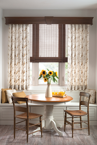 Tall drapes on each side of a large window in a small dining room