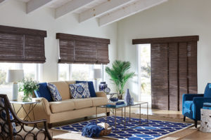 Woven shades rolled up halfway on multiple windows in a living room